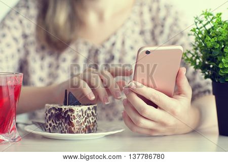 woman having breakfast in cafe and holding pink phone