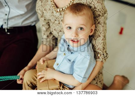 Nice portrait of attractive kid in bow-tie with parents at home. Looking at camera