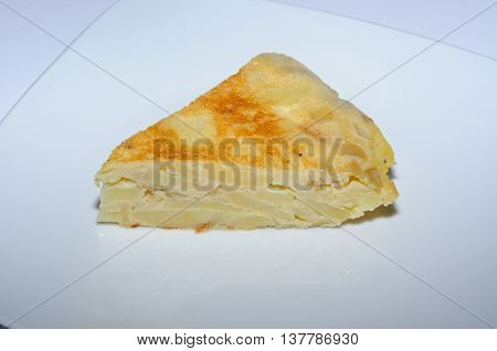 Wedge of Spanish tortilla on a white plate.