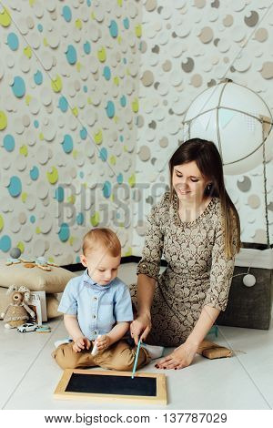 Attractive child with young mother draw at blank chalkboard indoors. Kid having fun at home. Boy in bowtie looking away. Blank chalkboard.