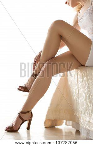 Beautiful woman sitting on bed and touching her leg. Beautiful slender legs closeup.