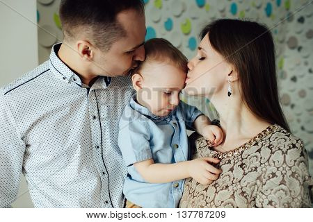 Nice portrait of happy family at home on fun background. Parents lovely kissing child.