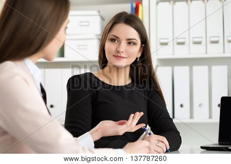 Two woman sitting at office and looking at laptop monitor discussing some questions. E-business distant education or business meeting concept