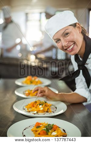 Portrait of female chef garnishing plate of food in commercial kitchen