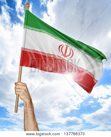 Person's hand holding the Iranian national flag and waving it in the sky, 3D rendering
