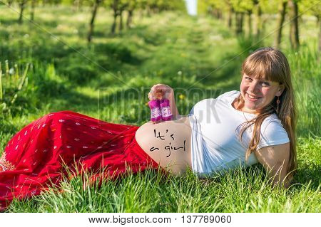 Pregnant Young Girl Lying On Grass In The Garden
