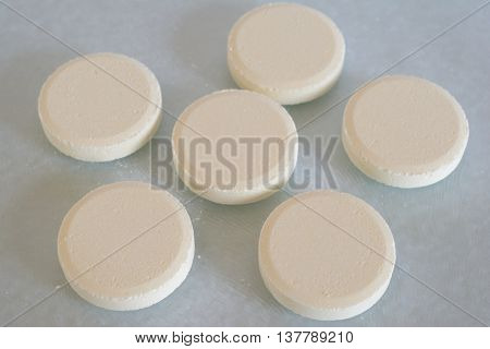Soluble tablets on glass table top closeup