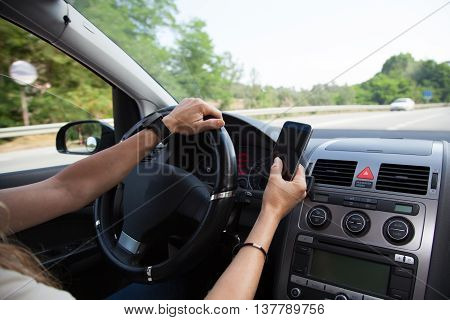Woman driving a car and using a mobile phone