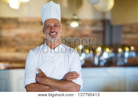 Portrait of smiling chef standing with arms crossed in restaurant