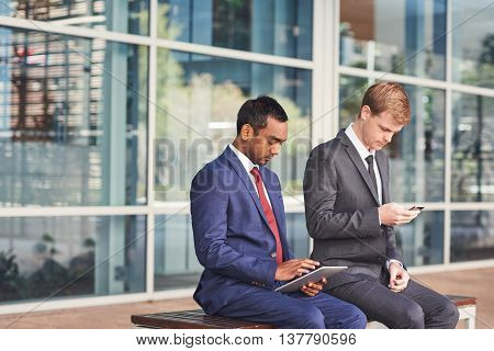 Two confident and successful businessmen sitting in front of the glass windows of a modern office building using a digital tablet and cellphone