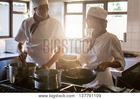 Chefs preparing food at stove in commercial kitchen