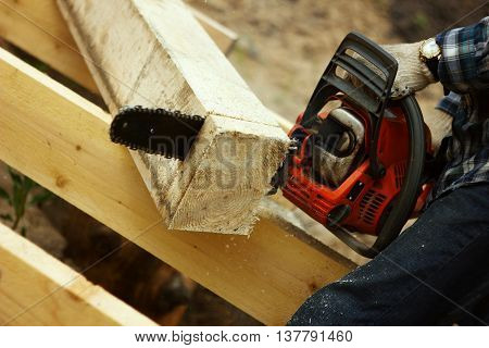timber sawing chainsaw outside in the summer with the clock gloves