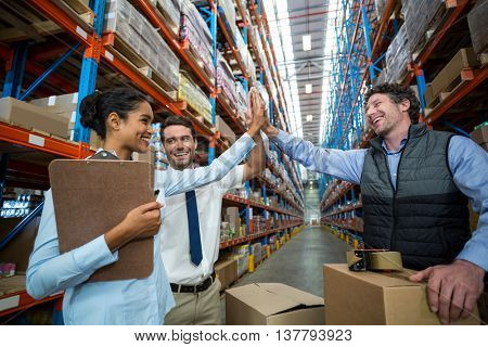 Happy managers are clapping hands each other in a warehouse