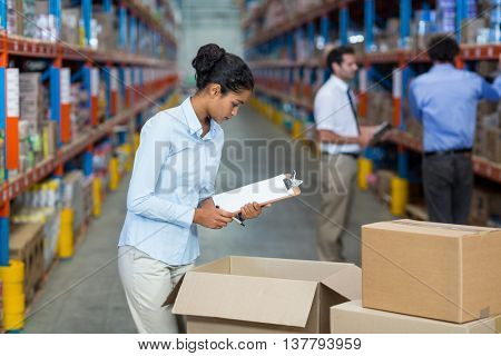 Focus of manager is checking some cardboard boxes in a warehouse