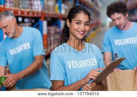 Portrait of happy volunteer is posing and holding a clipboard in a warehouse