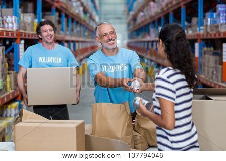 Woman gives some goods to volunteer in a warehouse