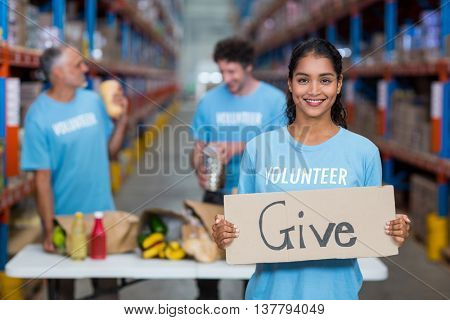 Portrait of happy volunteer holding a sign in a warehouse