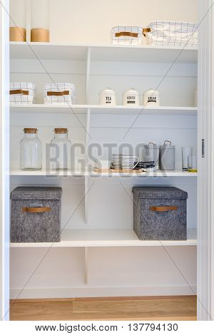 White Wooden Shelf Included Metal Boxes And Mugs With Bottles
