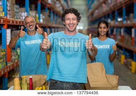 Portrait of happy volunteers are posing with thumbs up in a warehouse
