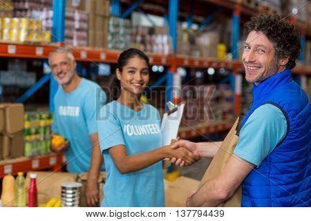 Portrait of happy volunteers handshaking in a warehouse