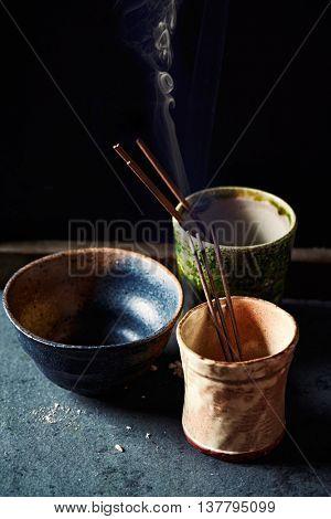 Natural incense sticks in ceramic cups