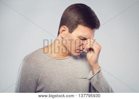 Feeling sick and tired. Frustrated young man massaging his nose and keeping eyes closed isolated on gray background