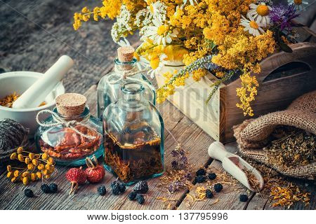 Bottles of tincture and dry healthy herbs wooden scoop bunch of healing herbs in wooden box on table. Herbal medicine. Retro styled. Selective focus.