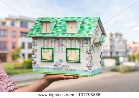 Real Estate Agent Holding Model House From Paper