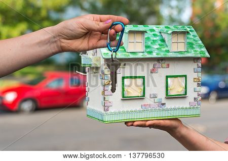Real estate agent giving house keys to a new property owner who is holding model house from paper on blurred background