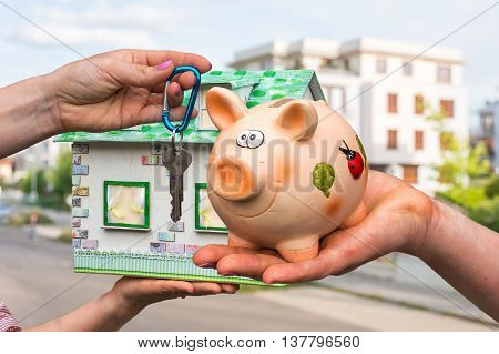 Real Estate Agent Giving House Key And Model House To A New Prop