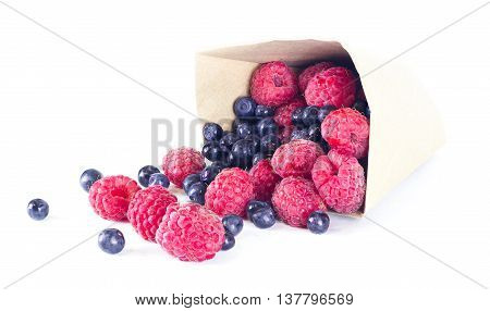 ripe raspberries and blueberries scattered from a package isolated