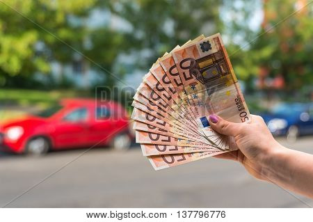 Car Buyer Holding Euro Banknotes And Buying A New Car From Sales
