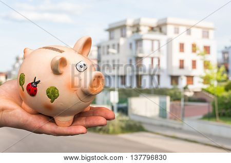 All savings money from pink ceramic piggy bank to pay for the dream home on blurred background
