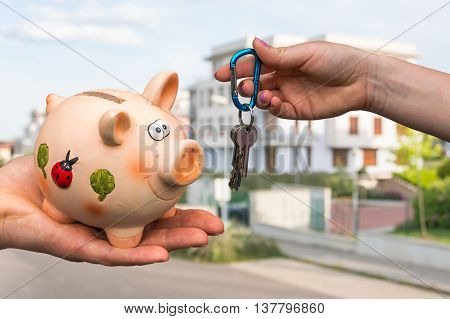 Real estate agent giving home keys to a new property owner who is paying all saving money from piggy bank on blurred background