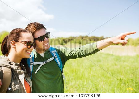 travel, hiking, backpacking, tourism and people concept - happy couple with backpacks walking outdoors and pointing finger to something