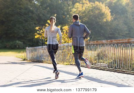 fitness, sport, people and jogging concept - couple running or jogging outdoors