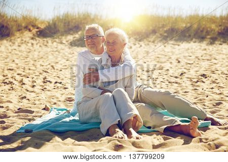 family, age, travel, tourism and people concept - happy senior couple sitting on plaid and hugging on summer beach