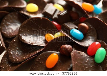 Chocolate chips and colorful candies, close up