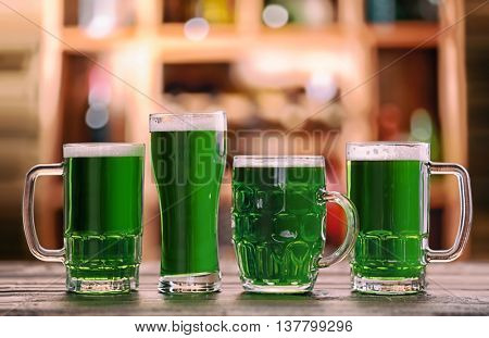 Different glasses of green beer on blurred bar background