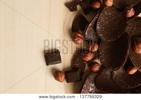 Chocolate chips and hazelnuts on wooden background