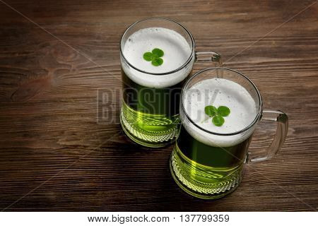 Glasses of green beer with clover leaves on wooden background