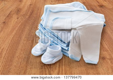 clothing, babyhood, motherhood and object concept - close up of white baby cardigan with bootees and pile of clothes for newborn boy on wooden table