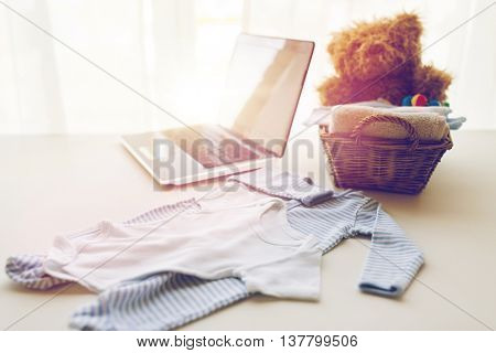 babyhood, motherhood, clothing, technology and object concept - close up of baby clothes and toys for newborn boy in basket with laptop computer at home