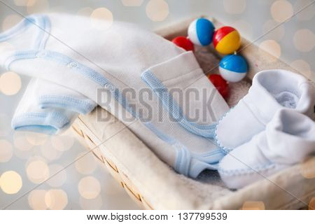 clothing, babyhood, motherhood and object concept - close up of white baby bootees with cardigan and rattle for newborn boy in basket on table