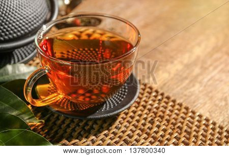 Traditional eastern teapot and teacup on wicker mat