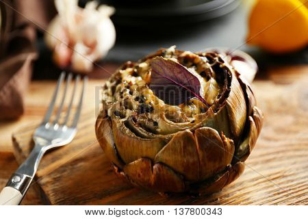 Baked artichoke on wooden cutting board, close up