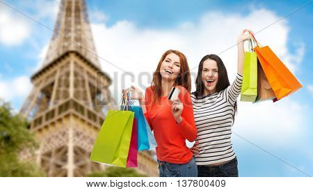 shopping, sale, tourism and people concept - two smiling teenage girls with shopping bags and credit card over paris eiffel tower background