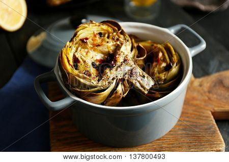 Baked artichokes in saucepan on cutting board, close up