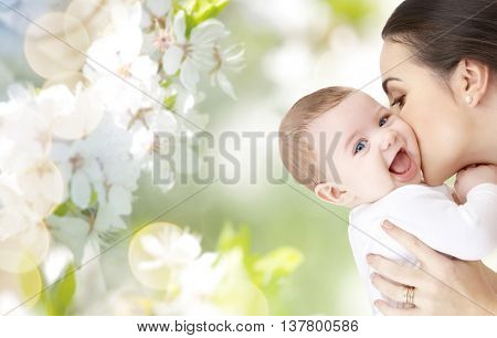 family, motherhood, parenting, people and child care concept - happy mother kissing adorable baby over green natural background