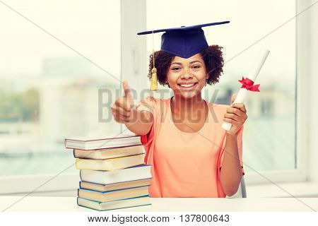 education, school, graduation, gesture and people concept - happy smiling african american student girl in bachelor cap with books and diploma sitting at table and showing thumbs up at home